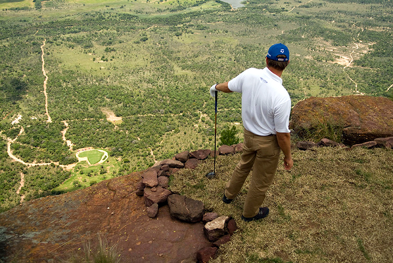 A golfer stands on a cliff ready to take a shot