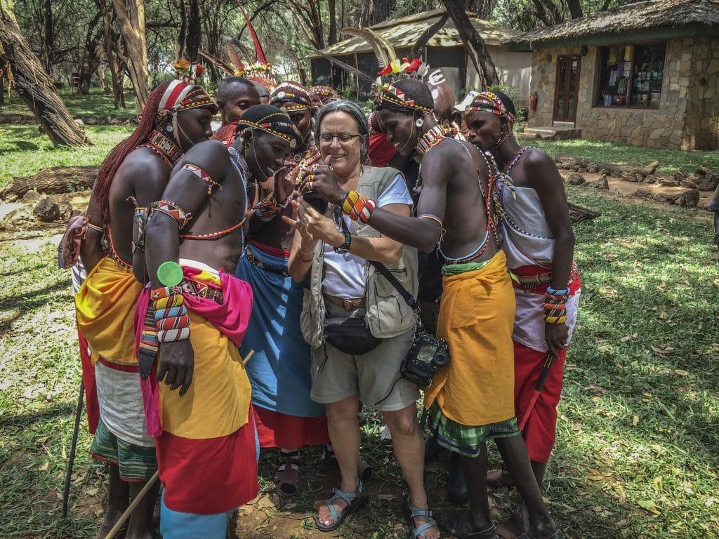 Samburu people look at a photo on a phone