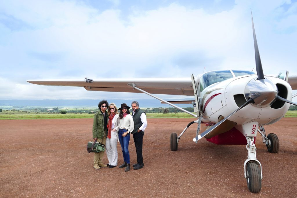 The pinto family in front of a plane