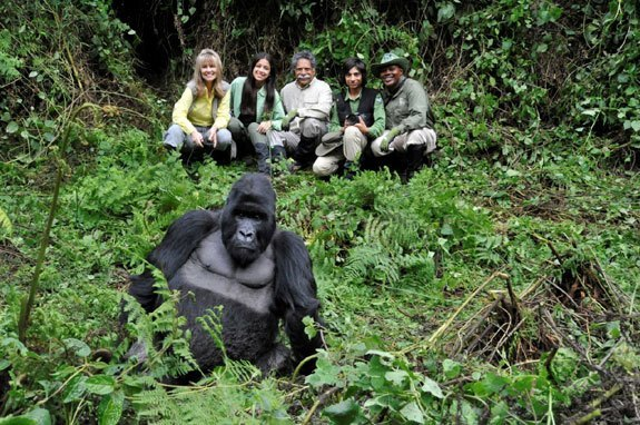 Safari travelers pose with a gorilla