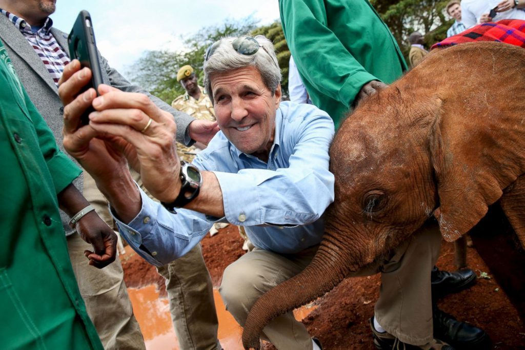 John Kerry taking selfie with elephant