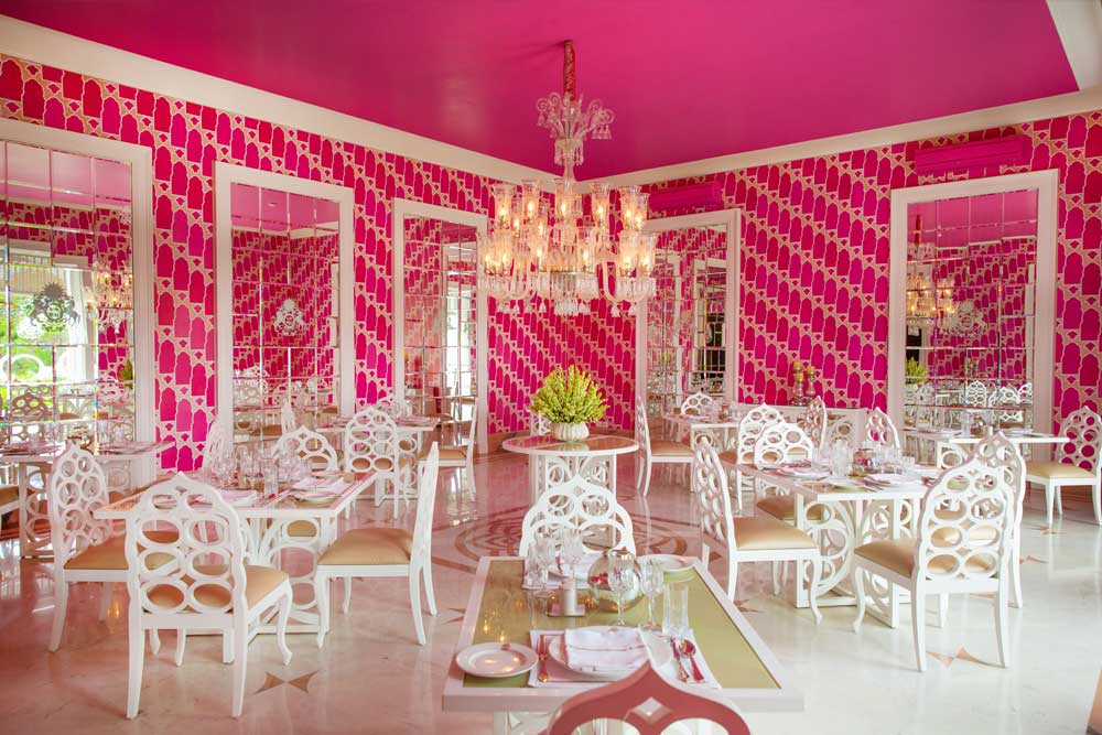 A pink room with tables, chairs, and a chandelier