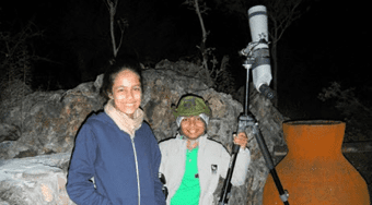The Pinto children standing next to a telescope.