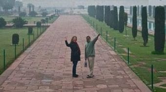 Two people wave in front of the Taj Mahal
