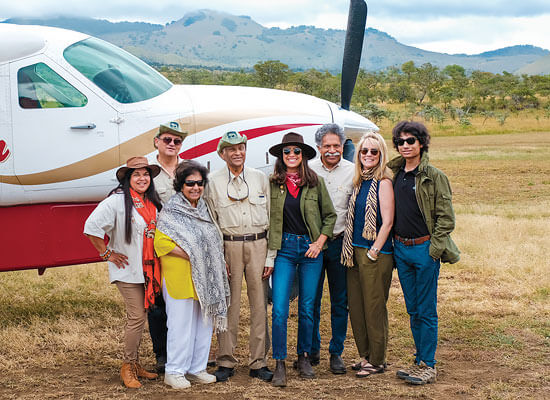A group of tourists in front of a byplane