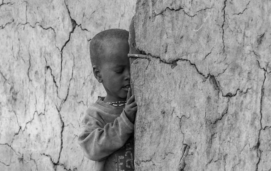 A little boy hiding behind a wall