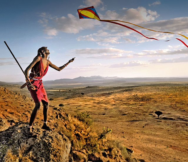 A Maasai warrior flies a kite over a valley with a beautiful landscape in background. Kenya, Africa.