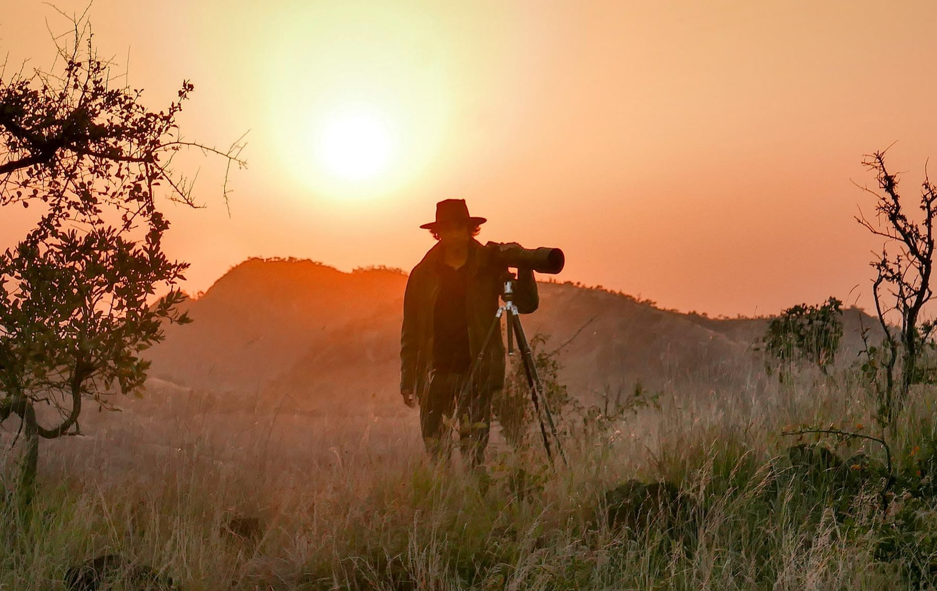 Man taking pictures during the beautiful sunset of Chyulu Hills