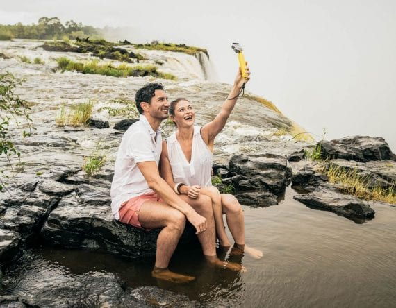 Couple taking selfie near waterfall