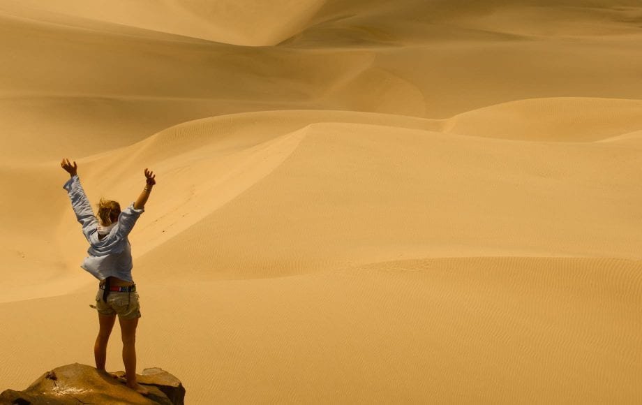 Joyful woman standing on top of the desert at Laikipia Plateau