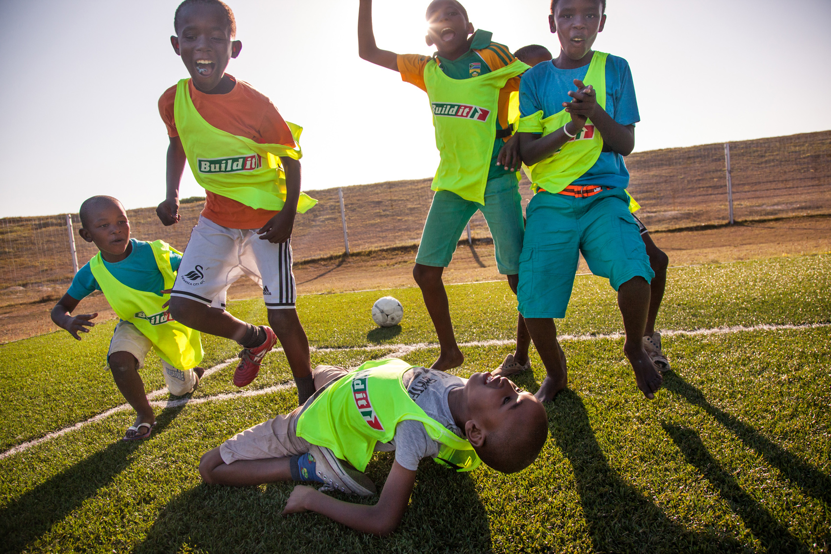 A group of children cheering on a soccer field.
