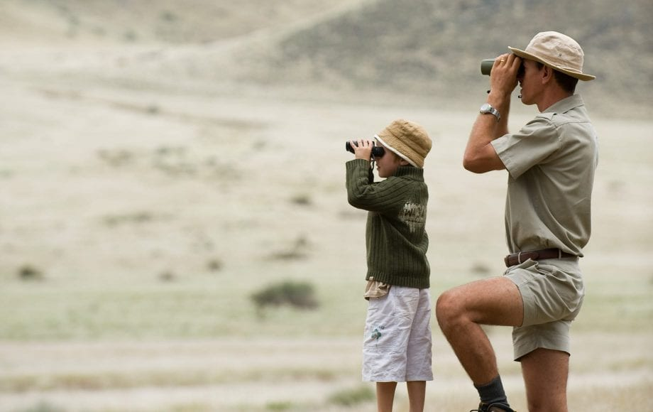 Boy and Man looking out using telescope at Sossusvlei Namib Desert