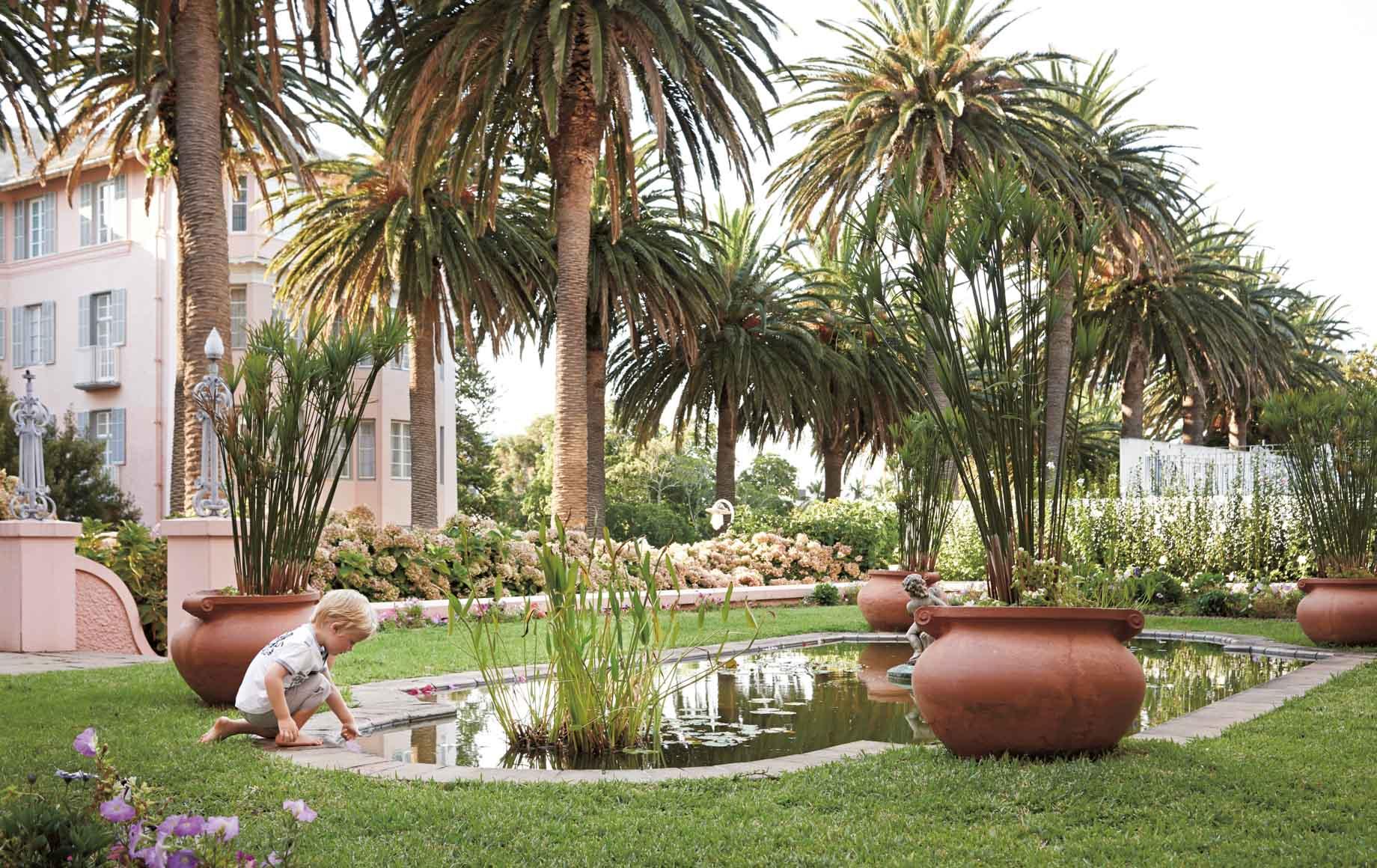 Boy plays in garden at Belmond Mount Nelson Hotel in Africa