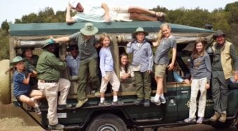 A family posing on a Micato Safaris truck.
