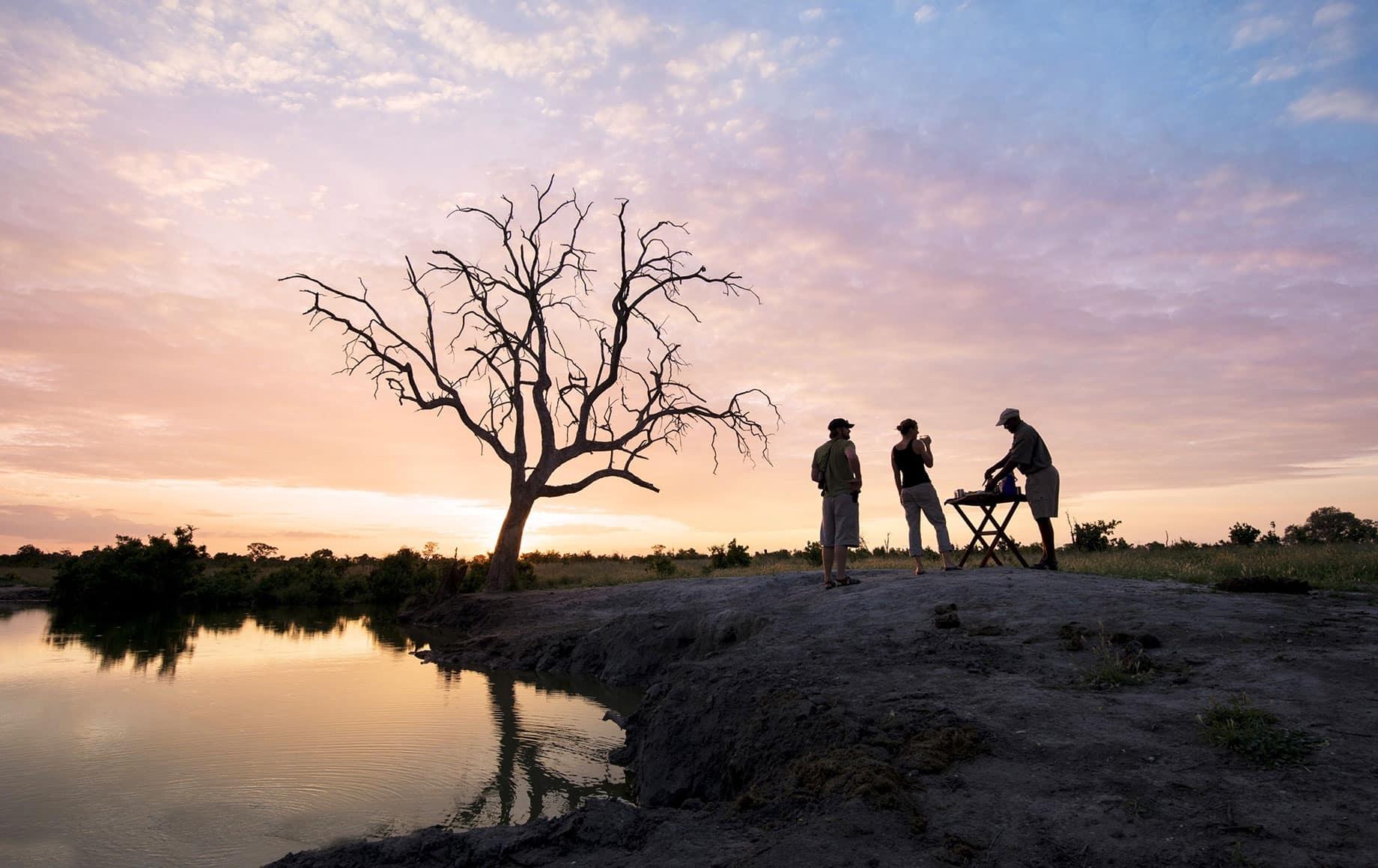 Travelers admire sunset near Somalisa Lodge