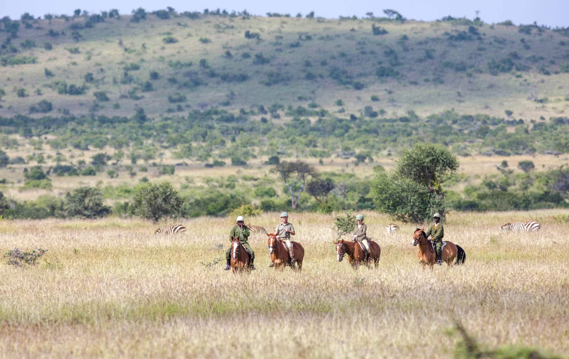 Safari-goers on horseback in Loisaba Conservancy