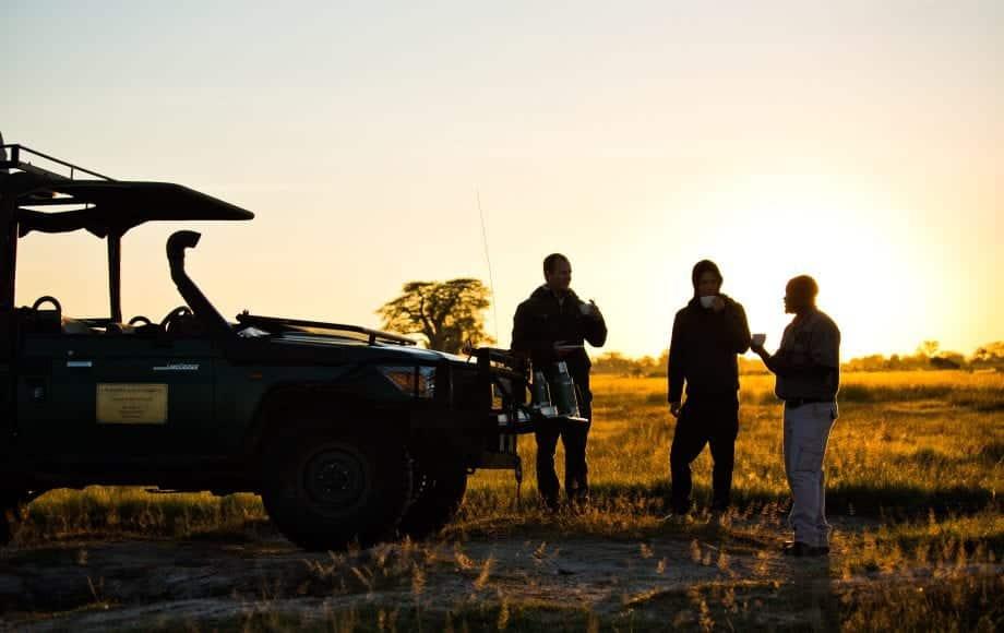 Safari-goers stand near vehicle at sunset