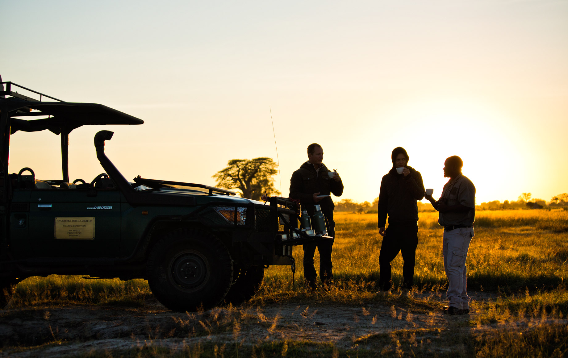 Safari-goers stand near vehicle at sunset