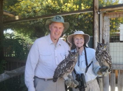 A man and a woman holding owls