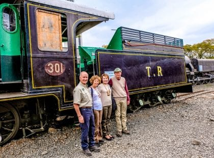 Friends posing for a photo in front of a train