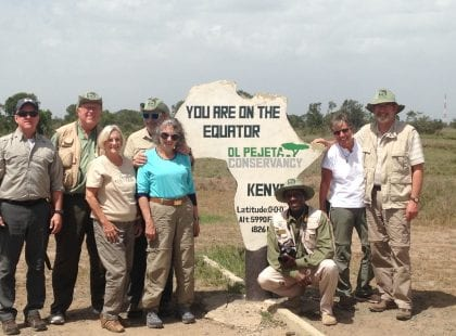 A group in front of a sign indicating the location of the equator