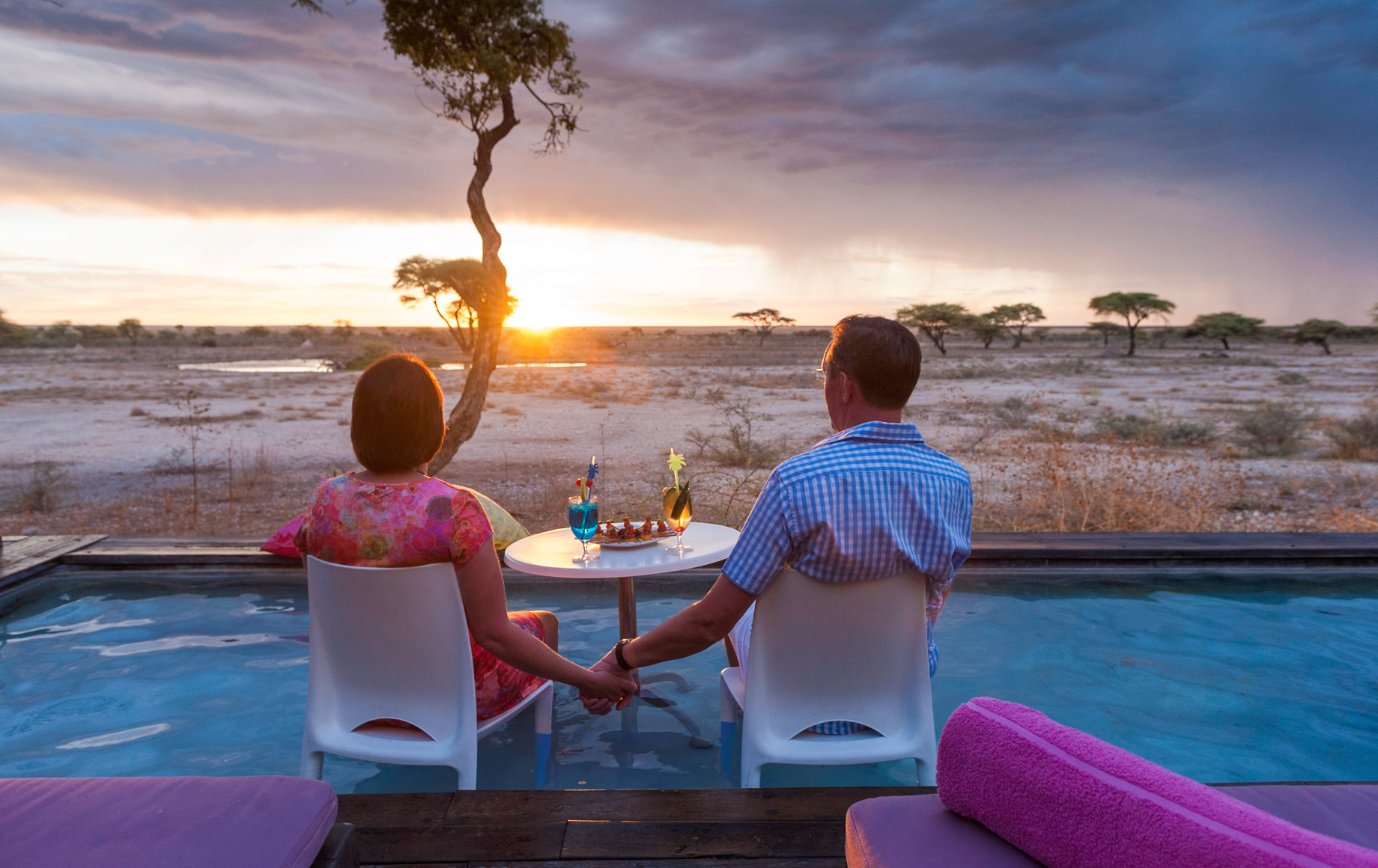 Couple sits at table in African evening