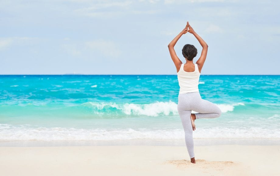 Woman does yoga on beach