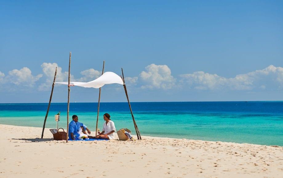 Couple picnics on beach near Park Hyatt, Zanzibar