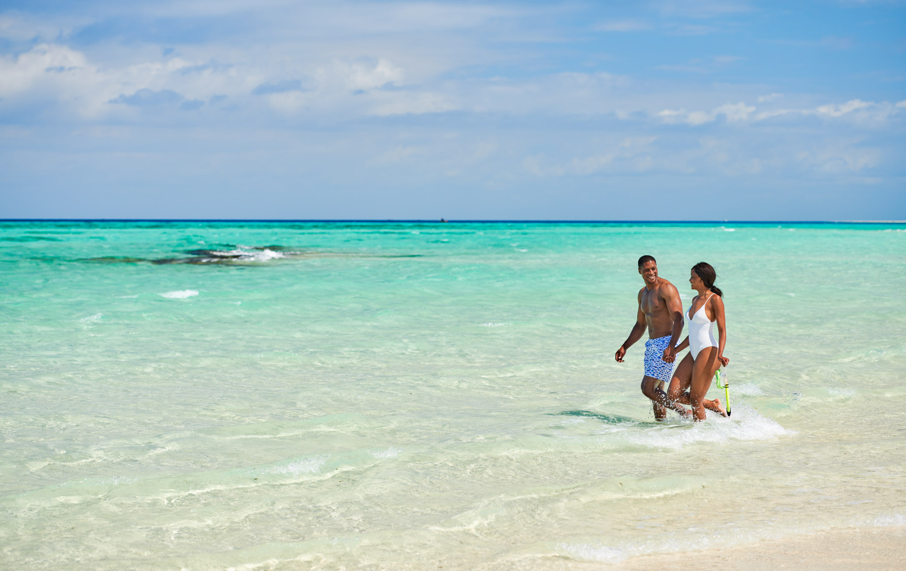 Couple walks along beach near Park Hyatt, Zanzibar