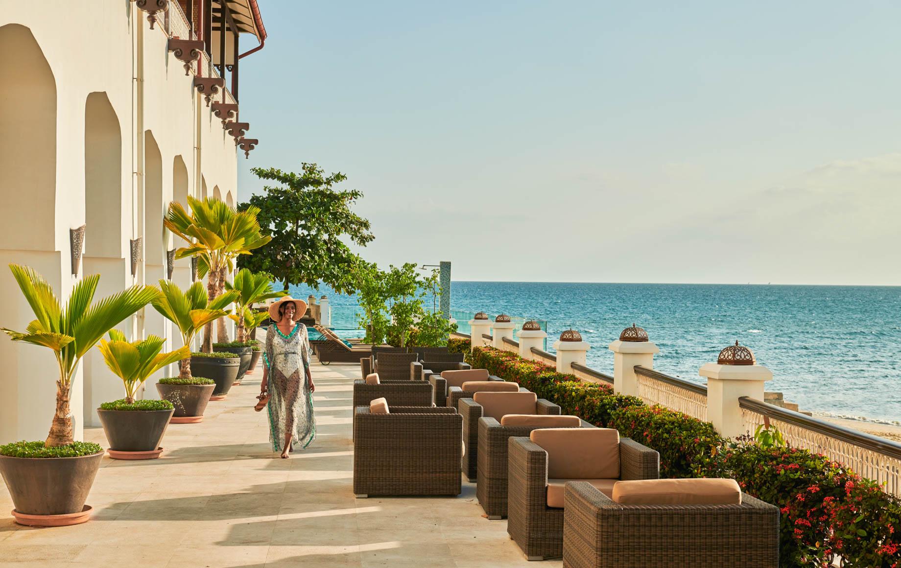Woman walks along deck of Park Hyatt, Zanzibar