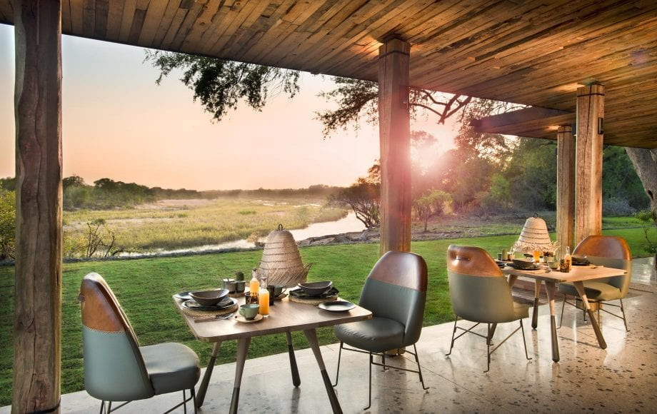 Tables and chairs on deck of Tengile River Lodge at sunset