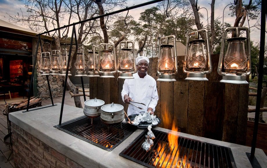 Chef cooks on outdoor grill at Thorntree River Lodge