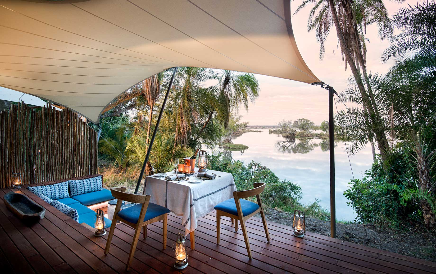 Table and lounge area on deck of Thorntree River Lodge