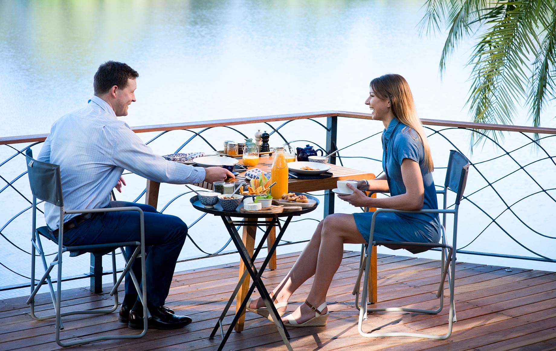 Man and woman sit at table on deck by river