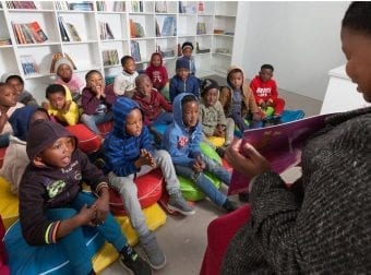Children happily sitting in a library