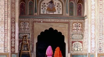 two ladies pass through doorway of Indian palace