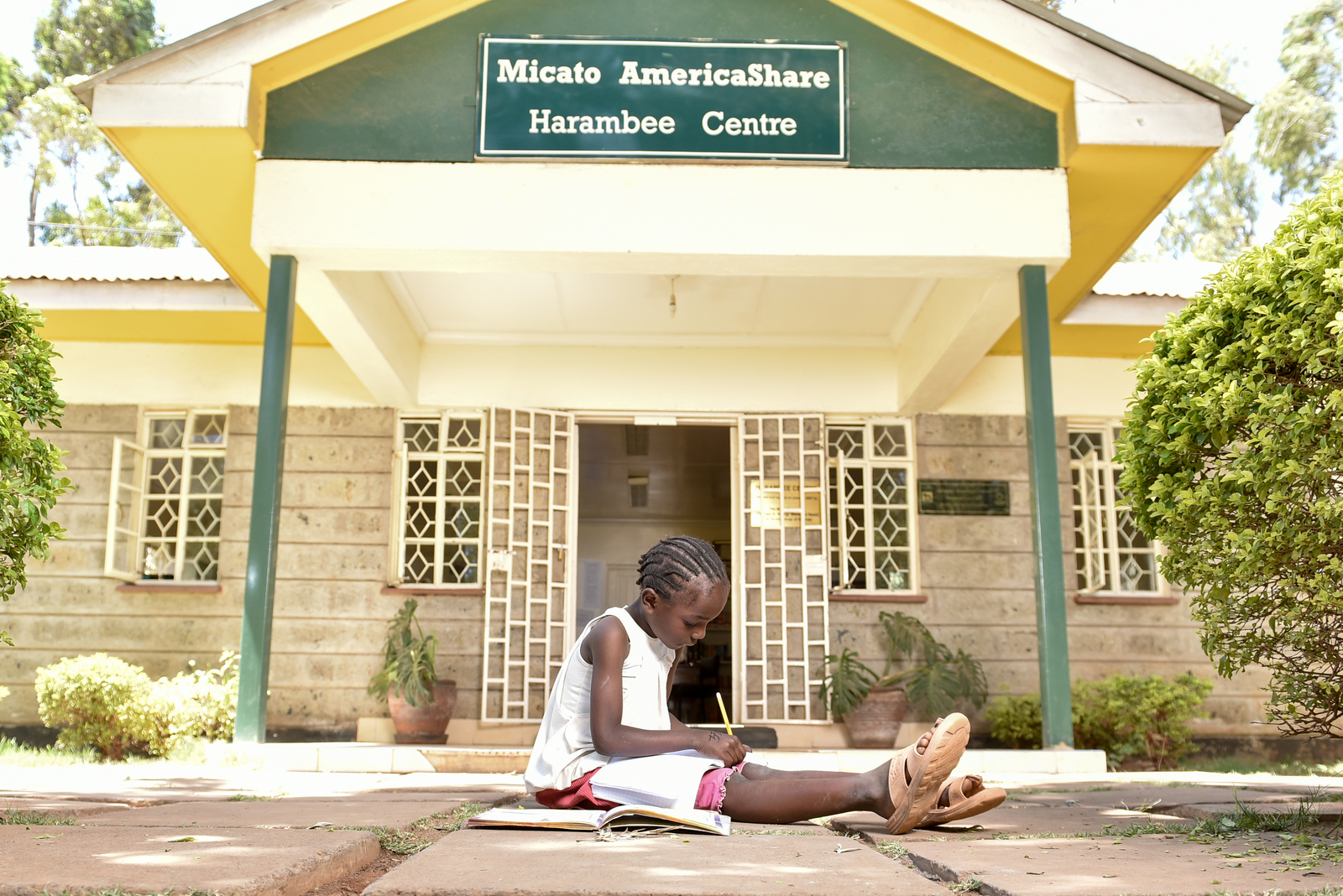 a girl sitting in front of the Micato AmericaShare's Harambee Centre