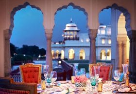A dinner table set overlooking a palace.