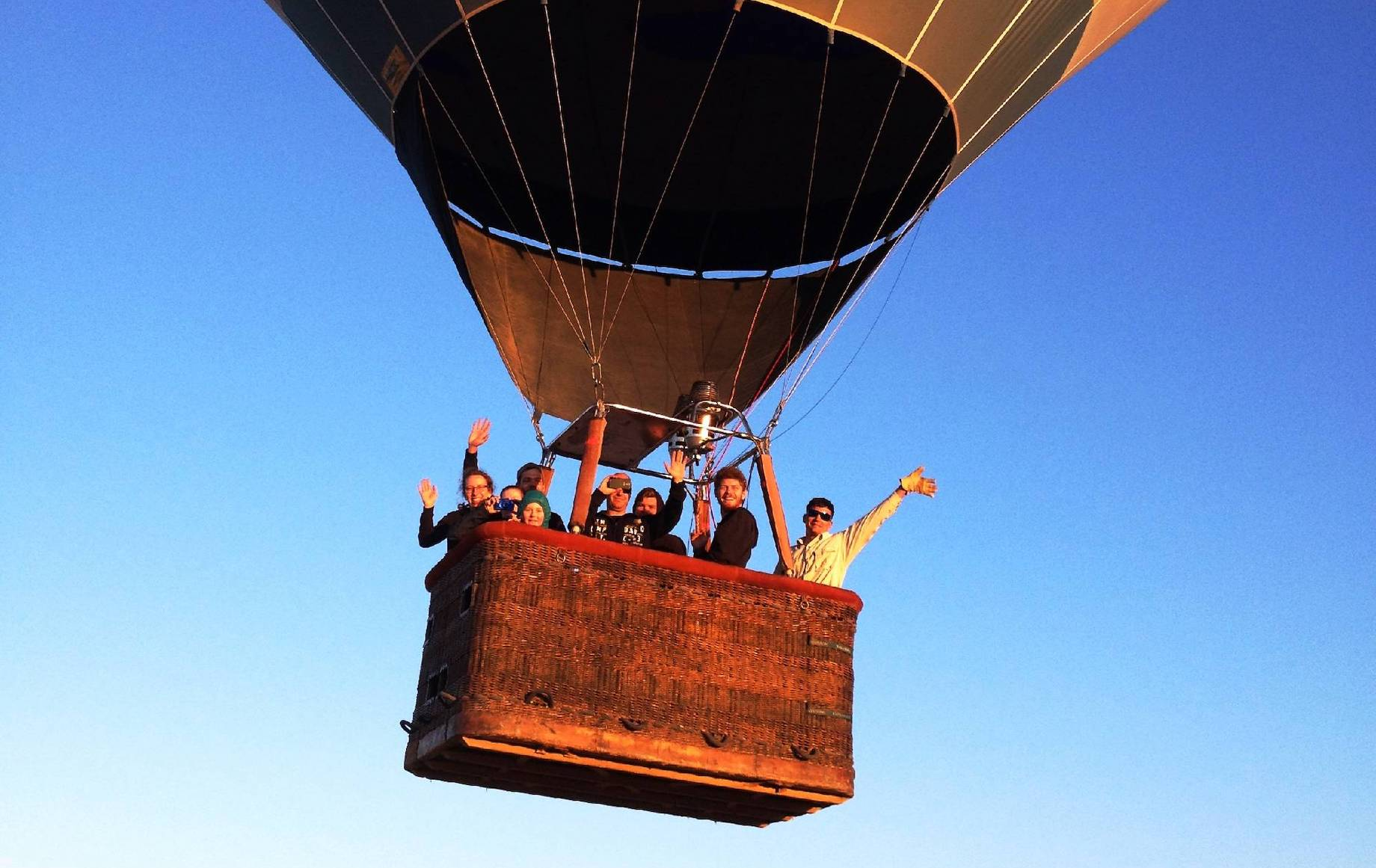 A group of travellers in the basket of a hot air balloon