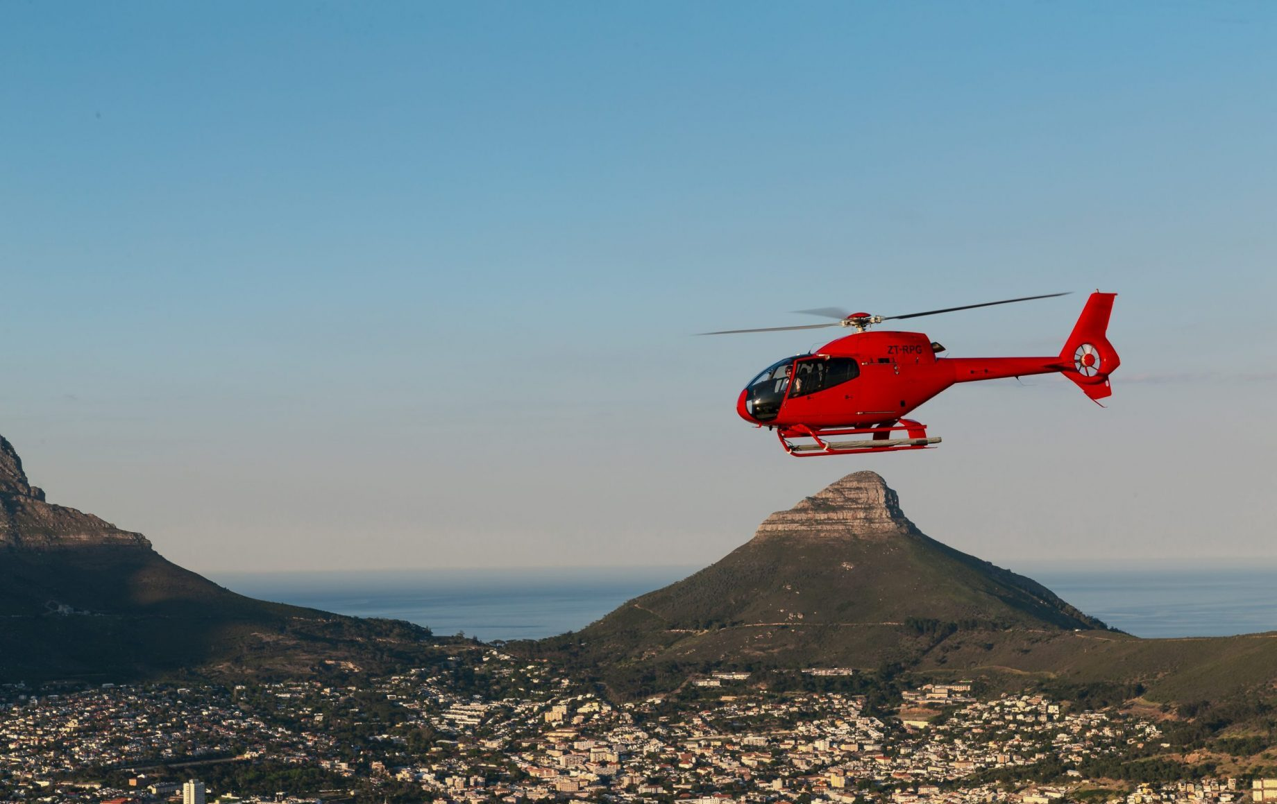 A red helicopter flying over cape town