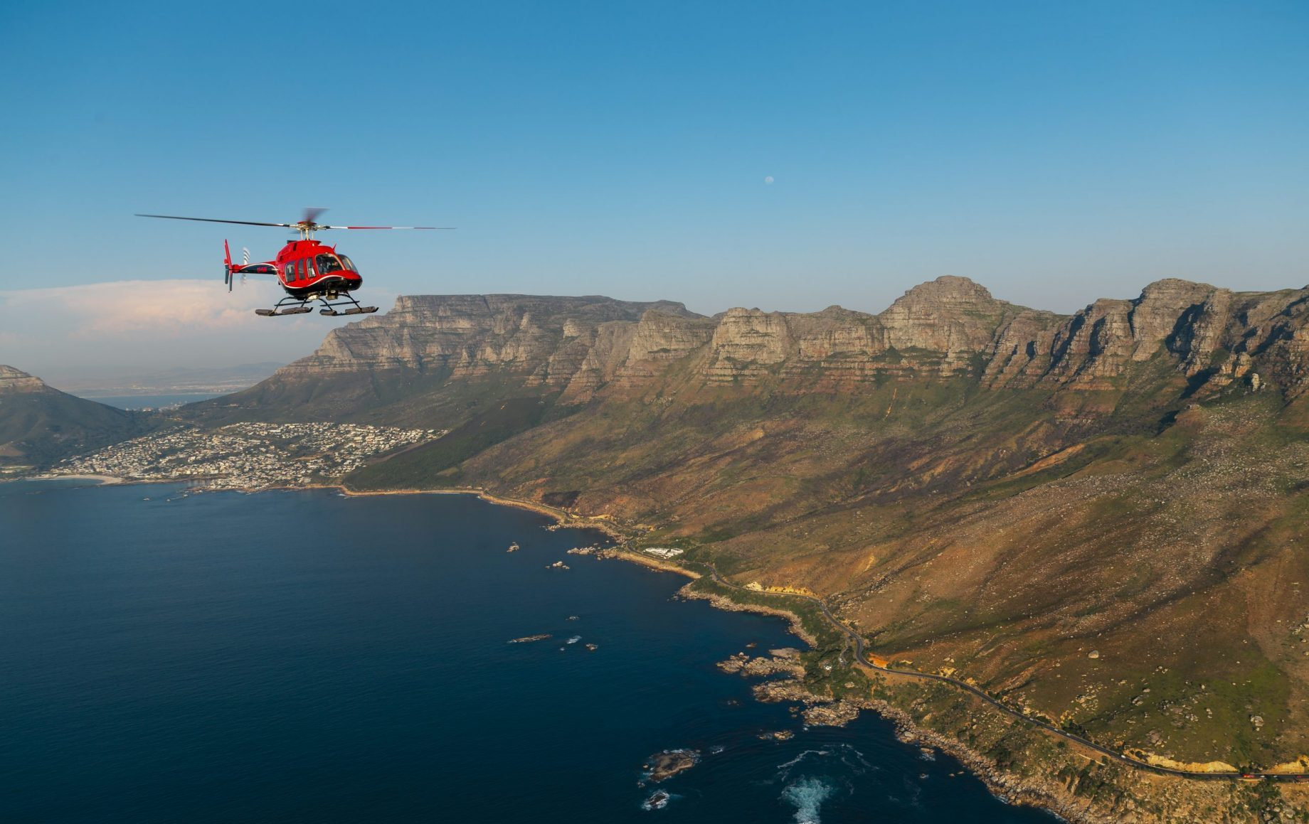 A helicopter ajacent to mountains of cape town