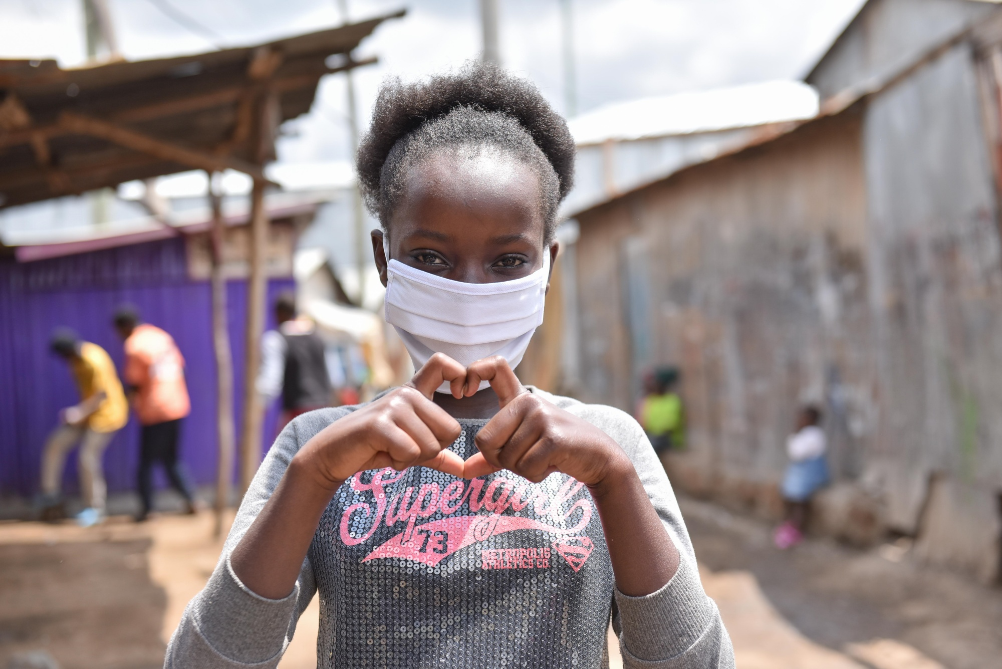 A young girl wearing a mask and making a heart with her hands