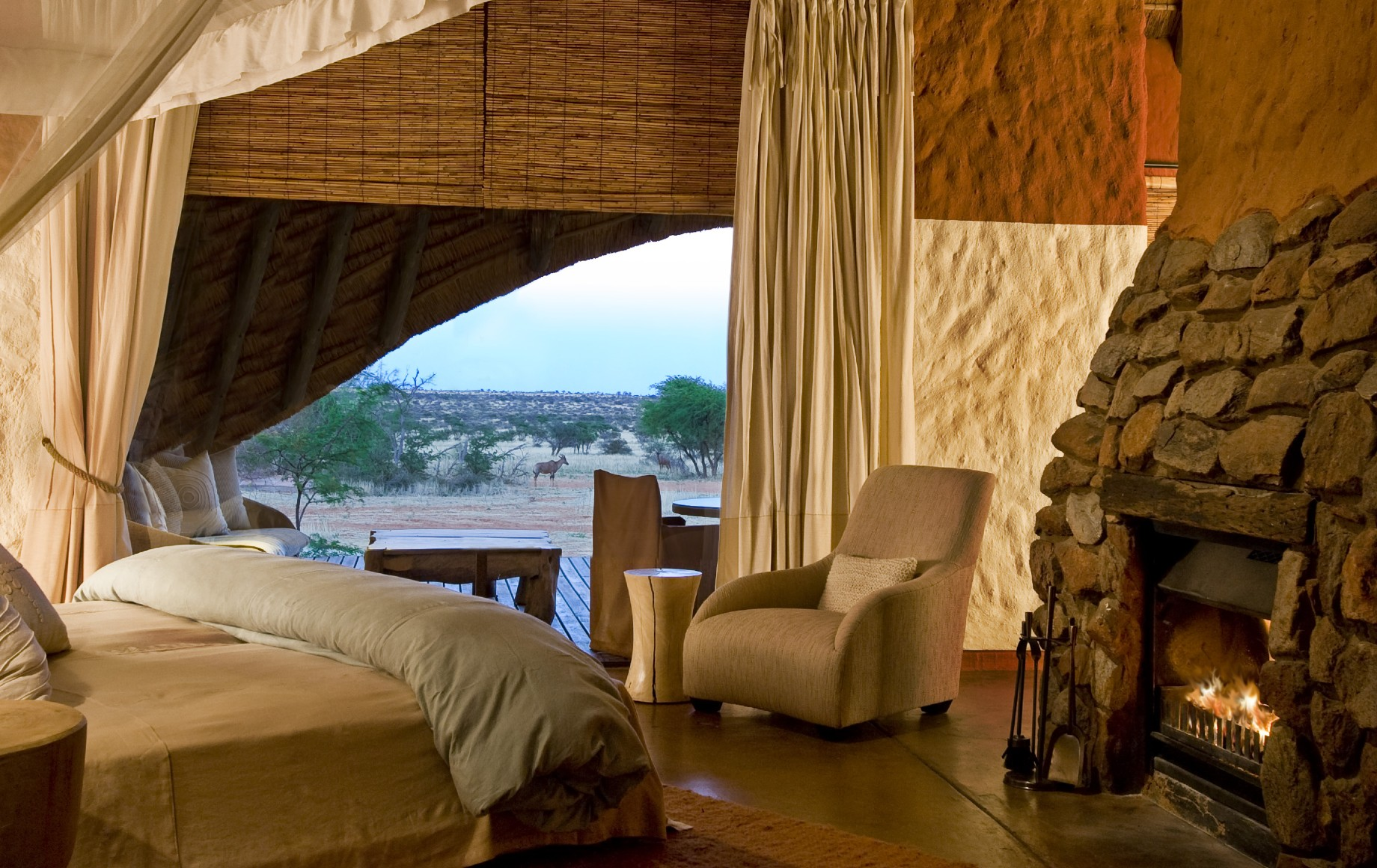 a bedroom with a fireplace at Tswalu Motse