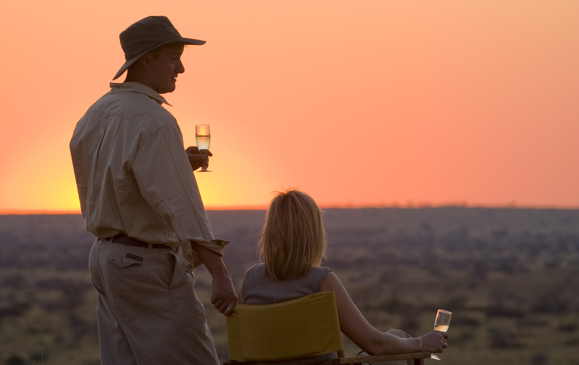 two people holding glasses of wine at sunset