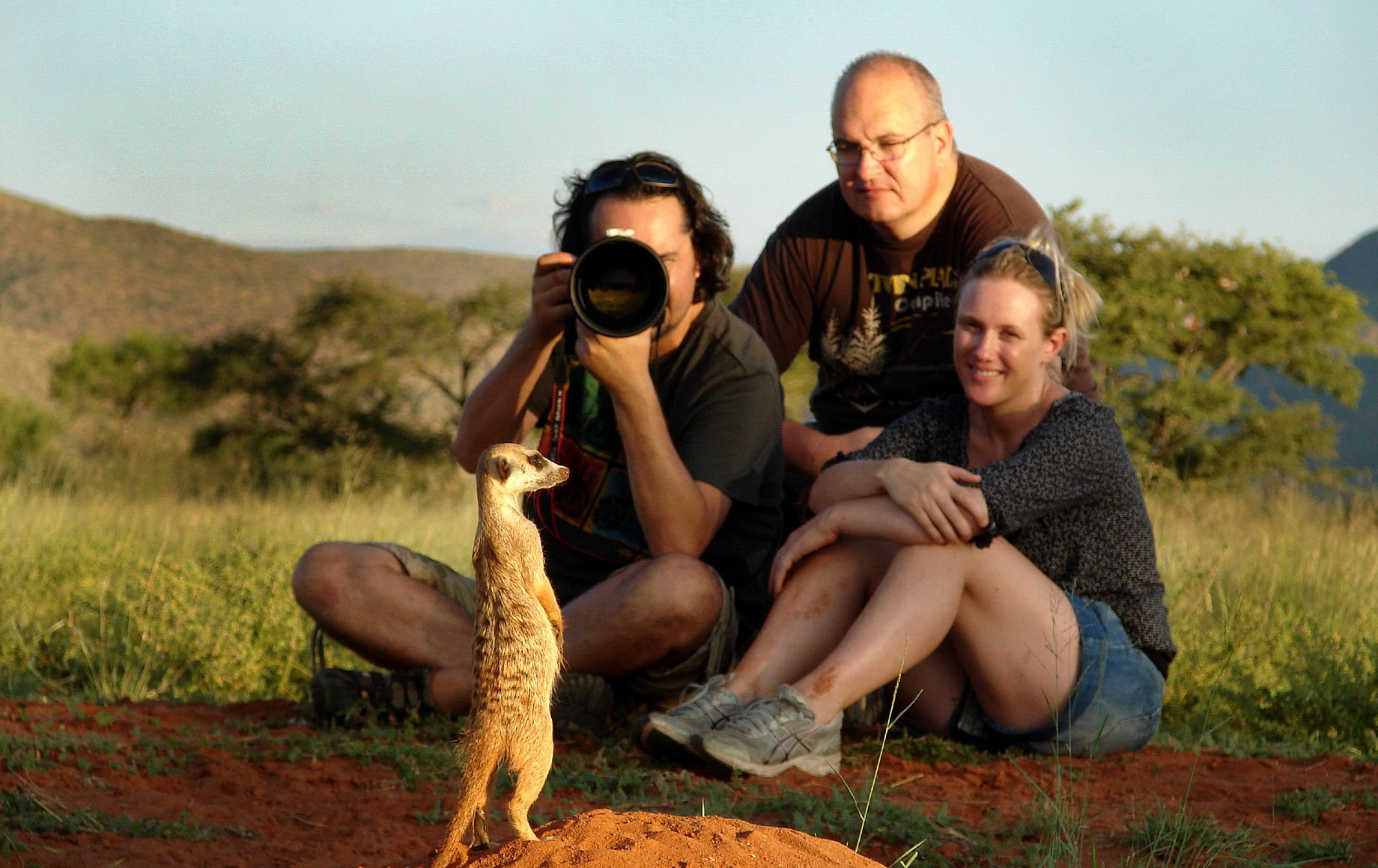 a man taking a photo of a meercat