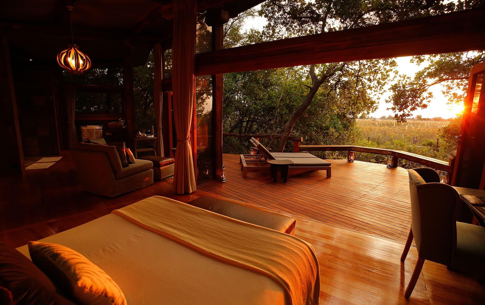 A bedroom at Camp Okavango at sunset