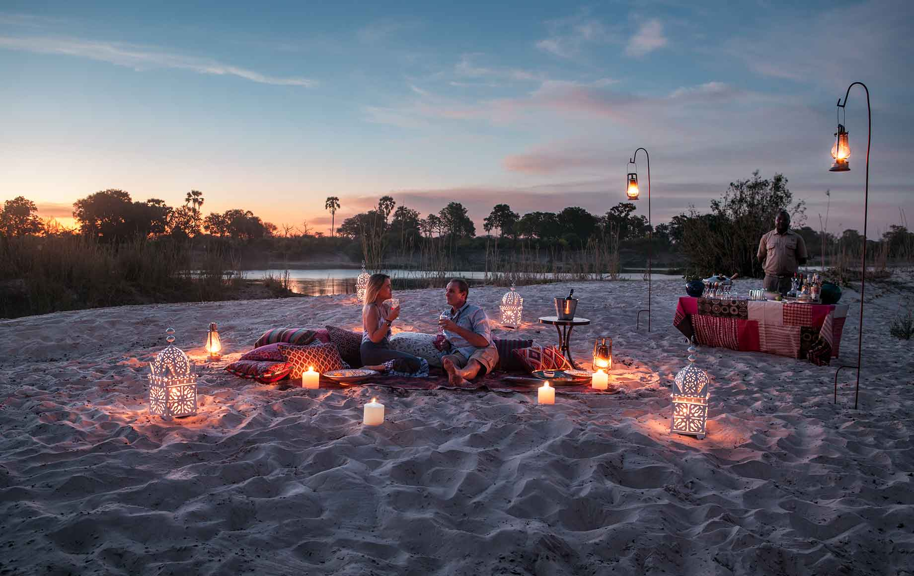 dinner on the beach surrounded by candlelight at Camp Tongabezi