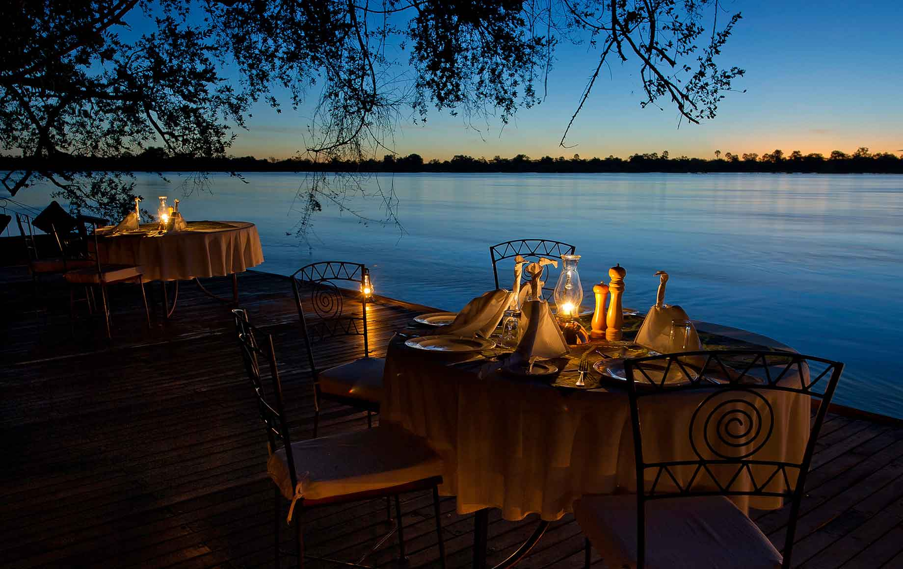 two tables set up for candlelit dinner near water at Camp Tongabezi