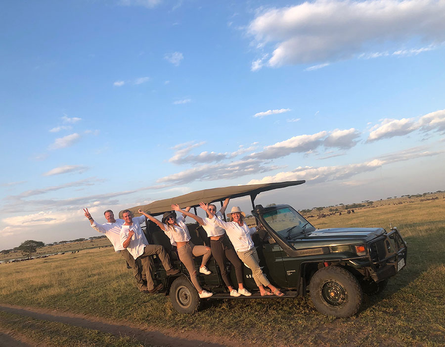 A group of people waving while hanging from the side of a jeep.