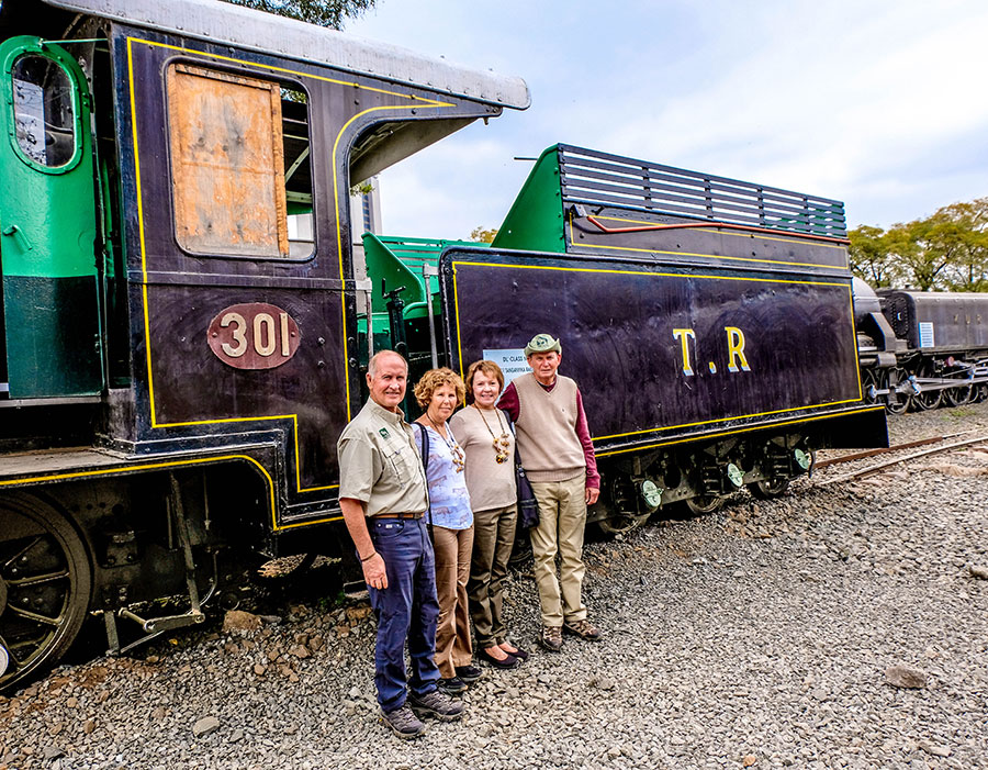 A group of people posing in front of a train